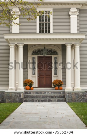 Front Door of Home showing two pillars with arch and twin flowerpots with four pumpkins, 2 on each side. Shows stone tile walkway leading to front entrance.