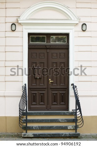 Front door of old house and decorative metal handrail