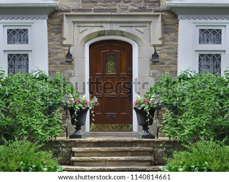 front door of stone faced house with shrubs #1140814661