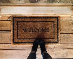 Front door welcome mat at rustic cabin