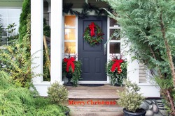 Front door with a Christmas wreath and bows. Merry Christmas stencilled on the front step.