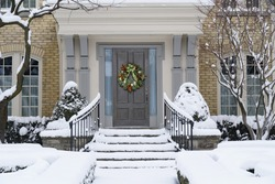 Front door with decorative seasonal or Christmas wreath, and snow covered shrubbery