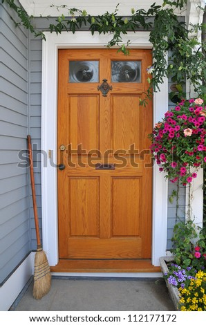 Front doorway adorned with flowers and greenery and swept clean welcomes visitors