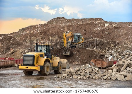 Front end loader and excavator at landfill for disposal of construction waste. Gravel and concrete crushing. Recycling old concrete and asphalt from demolition. Salvaging, removal building materials Photo stock ©