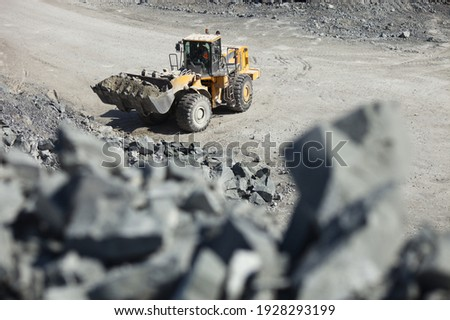 Front end loader, close-up, while working in a limestone quarry, top view with large stones in the foreground out of focus.  Mining industry. Foto stock ©