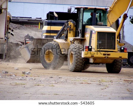 Front end loader drives through construction site.