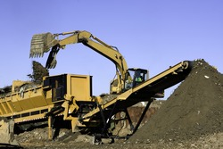 Front end loader dumps landfill into a screener to separate solid waste from good soil which is transported by conveyor belt to preserve landfill space.