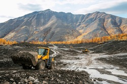 Front-end loader in the mode of transporting mountain soil. Earthworks in mountainous areas.
