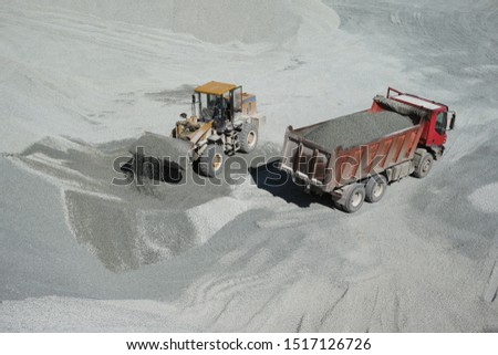 Front end loader loaded a full bucket of crushed stone while loading a dump truck at a mining enterprise. #1517126726
