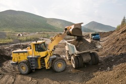 Front-end loader loads gold-bearing mountain soil into the back of a mining truck in a mountainous area. Eastern Siberia.