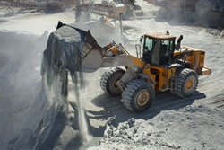Front end loader pours out a small stone fraction from the bucket against the background of the equipment of the ore-dressing plant, close-up.