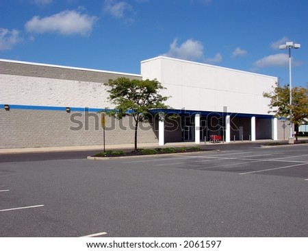 Front entrance of a vacant big box brick and mortar retail store and empty parking lot available for real estate lease or sale