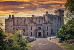 Front entrance of Dunvegan Castle on the Isle of Skye, Scottish Highlands at Loch of Dunvegan, in a dramatic sunset, Scotland, UK