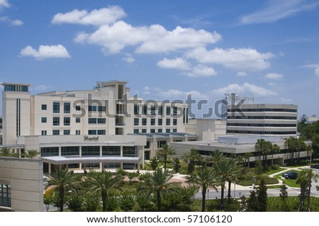 Front entrance to a hospital with palm tree landscaping and blue sky