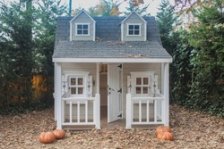 Front facade of a playhouse with a portico, door open, in a garden with pumpkins and fallen leaves, at fall.