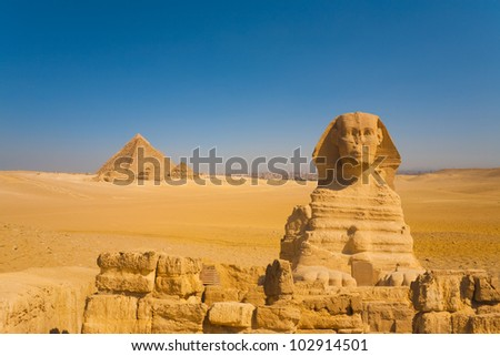 Front face of Great Sphinx in vast desert with distant set of Giza pyramids on a clear sunny, blue sky day with the city of Cairo in the background, Egypt. Horizontal copy space