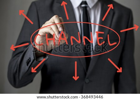 "Front faced businessman is writing ""CHANNEL"" on the board (focus on hand, blur out the suit)."