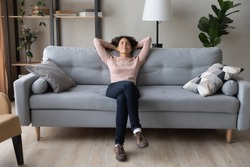 Front full length view tranquil millennial pretty woman relaxing on comfortable sofa in living room. Peaceful young lady sleeping, reducing stress, enjoying lazy weekend time on sofa alone at home.
