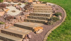 Front garden rockery with outside staircase made of sandstone and concrete pavement