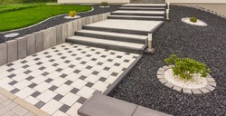 Front garden with external staircase made of prefabricated concrete parts concrete paving and stelae