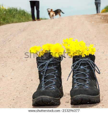Front hiking boots and in the background people with dog
