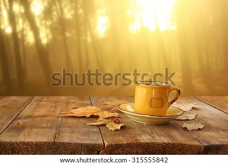 front image of coffee cup over wooden table and autumn leaves in front of autumnal sunset background