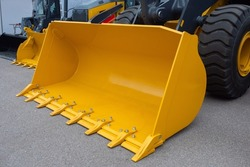 Front loader bucket. Yellow loader bucket close up. Fragment of loader. Special equipment for construction work. Special equipment for loading operations. Machinery for agricultural activities.