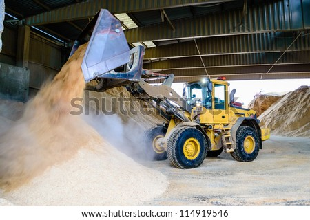 Front loader emptying wood chips in pile for use in pellets manufacturing.