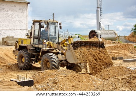 front loader leveled and pour sand in construction site