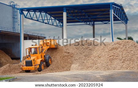 Front loader loading wood chips in pile in warehouse. Loader works at wood chips storage yard. Alternative ecological fuels. Sawdust processing, woodchip biomass heap. Pellets manufacturing Foto stock ©