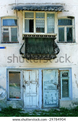 Front of a building with balcony, door and windows