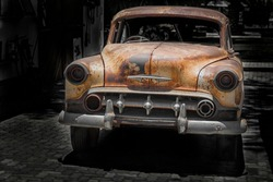 front of a parking  antique car with chrome bumper and grill, rusty fenders and hood and broken head lamps