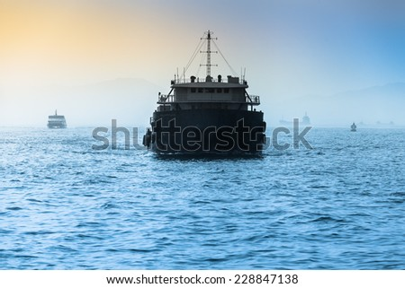 Front of a small cargo vessel at the evening sea with further ships at the background horizon/Freight Ship at Wide Sea