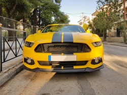 Front of a yellow sport car with black stripes.