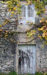 Front of an old rural stone house with the typical arbor over the entrance door in Lugo Galicia