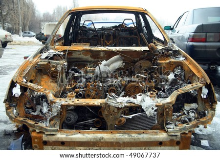 front of burnt out abandoned car - stock photo
