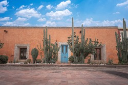 front of house with colonial architecture of a magical town in Queretaro Mexico, blue door and orange wall with green cactus