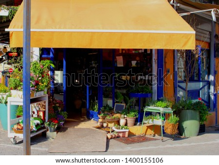 Front of small floristry shop with orange awning and outside display of blooming flowers, garden plants, pots and home design decorations Photo stock ©