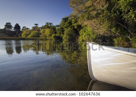 Front of small wooden row boat, with reflections, Lake Rotorua, New Zealand