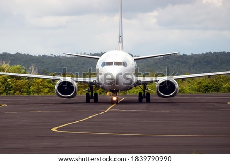 Front of White Commercial Airplane with Mountain Background