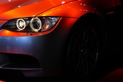 Front part of a coupe sports car under a red spot light. No logo shown.