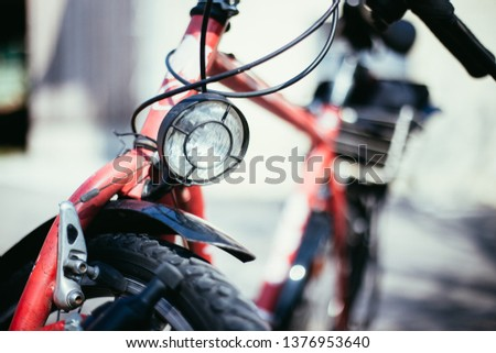 Front picture of a city bike, head lamp and blurry background
