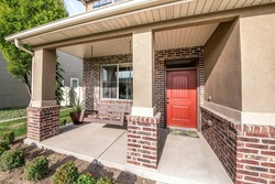 Front porch exterior with red orange door and res bricks siding