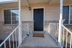Front porch of a house with metal railings and concrete doorsteps