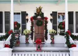 Front porch of a Key West style home in Florida decorated in holiday wreaths and bows for Christmas