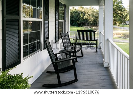 Front Porch of Southern home with Black Rocking Chairs and a Casual Feel #1196310076