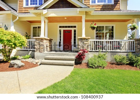 Front porch of the American house with red door.