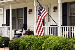 front porch of white colonial home with black shutters and american flag