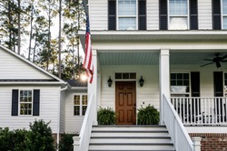 Front Porch with Stairs of All American White Farmhouse with Wood Doors