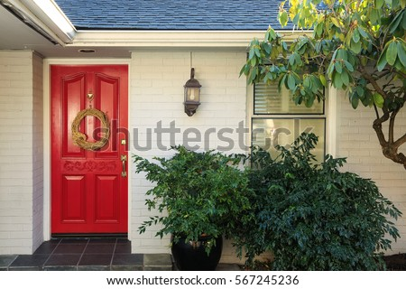 Front porch with white painted brick exterior, red entrance door accented with Door Wreath and finished with pot planter under wall lantern. Northwest, USA
